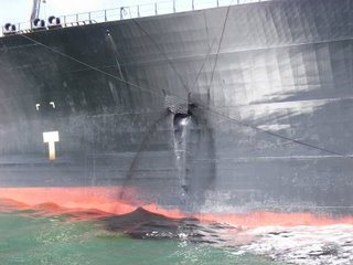 The Hebei Spirit leaks oil from tank No.5 at a much slower pace due to the quick use of 'rigged matting' held across the hole.